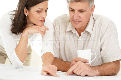 Buy stock photo Portrait of a beautiful mature couple looking over paperwork