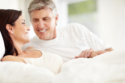 Buy stock photo Portrait of happy mature couple lying in bed and looking at each other