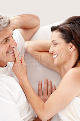 Buy stock photo Portrait of happy mature couple lying in bed together and smiling