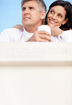Buy stock photo Portrait of happy mature couple having coffee together and looking away against sky
