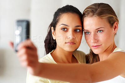 Buy stock photo Portrait of pretty young females taking picture of themselves from mobile phone