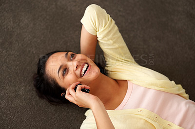 Buy stock photo Charming young woman enjoying conversation on mobile phone while lying on the floor