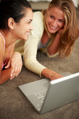 Buy stock photo Portrait of charming young females working together on laptop while lying on the floor