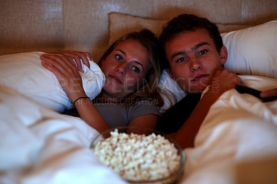 Buy stock photo Portrait of a cute young couple watching television while lying on the bed