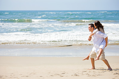 Buy stock photo Full length of a young man giving piggyback to woman on beach. Couple in love on a sunny beach holiday.
