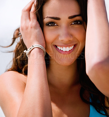 Buy stock photo Close up portrait of a beautiful young lady smiling. Holding her hair.