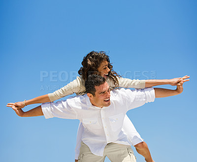 Buy stock photo Laughing young man giving piggyback to woman against blue sky. Arms stretched out together.