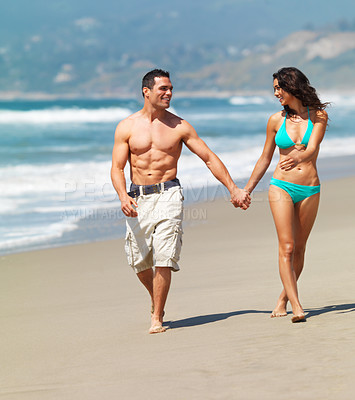 Buy stock photo A smiling young couple walking on the beach
