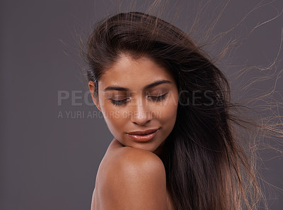 Buy stock photo Shot of an attractive young woman with windswept hair in studio