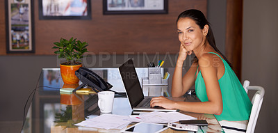 Buy stock photo A beautiful young woman looking content as she works from her home office
