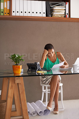 Buy stock photo A young businesswoman reading through documents in her home office