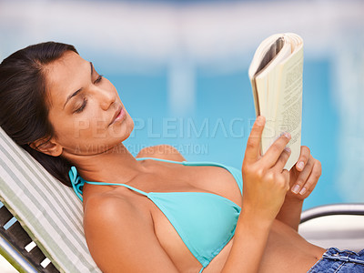 Buy stock photo A beautiful young woman reading a book while relaxing in a lounge chair by a swimming pool