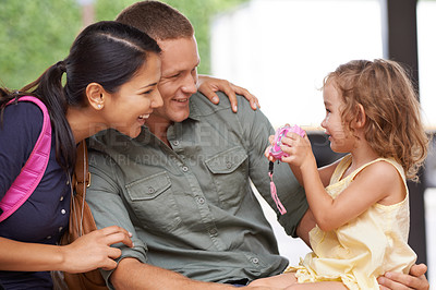 Buy stock photo A family bonding outdoors while waiting for their bus to arrive