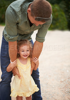 Buy stock photo A father holding on to his adorable little girl as they stand outdoors