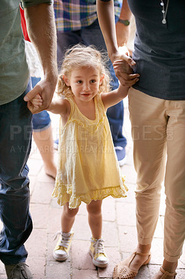 Buy stock photo An adorable little girl holding her parent's hands while walking through the street