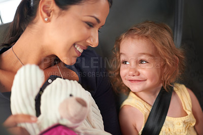 Buy stock photo A beautiful mother and daughter keep each other entertained while travelling at the back of a car