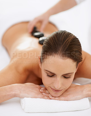 Buy stock photo Cropped shot of a gorgeous young woman enjoying a hot stone massage
