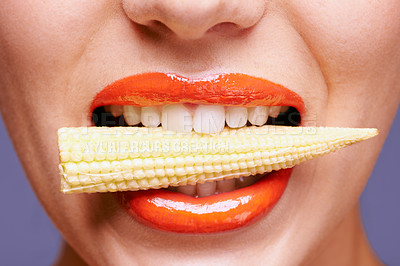 Buy stock photo Cropped shot of a beautiful young woman eating baby corn