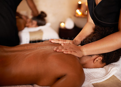 Buy stock photo Shot of a massage therapist giving a woman a massage at a day spa