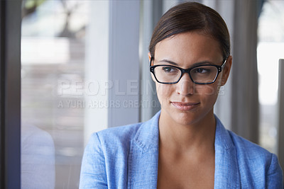 Buy stock photo Shot of a successful young businesswoman standing by a window and looking thoughtful