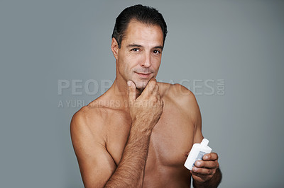 Buy stock photo Studio portrait of a handsome mature man holding a bottle of moisturizer