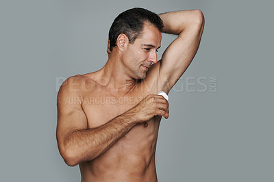 Buy stock photo Cropped studio shot of a handsome mature man applying deodorant to his underarms