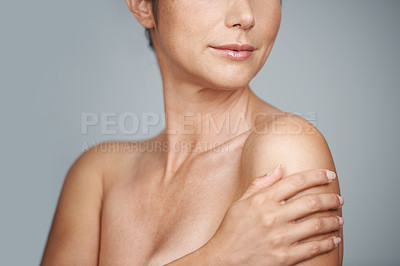 Buy stock photo Studio portrait of a beautiful mid adult woman standing with her hand on her shoulder