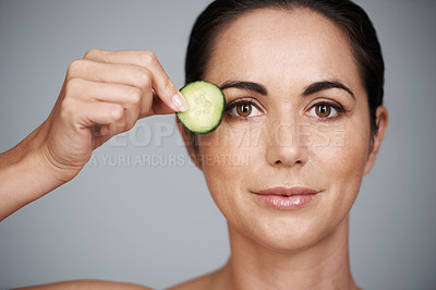Buy stock photo Studio shot of a beautiful mid adult woman holding a slice of cucumber to her face