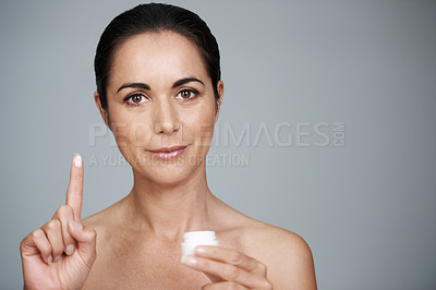 Buy stock photo Cropped portrait of a beautiful mid adult woman showing the moisturizer she uses