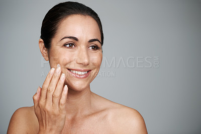 Buy stock photo Cropped shot of a beautiful mid adult woman applying moisturizer to her skin