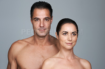 Buy stock photo Studio portrait of a mature man and woman standing close together against a gray background