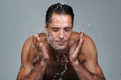 Buy stock photo Studio shot of a handsome mature man splashing water onto his face