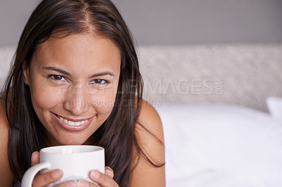 Buy stock photo Portrait of an attractive young woman relaxing on a bed with a warm drink