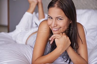 Buy stock photo Cropped portrait of an attractive young woman lying on a bed