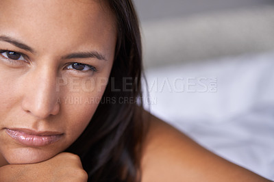 Buy stock photo Closeup portrait of an attractive young woman lying on a bed