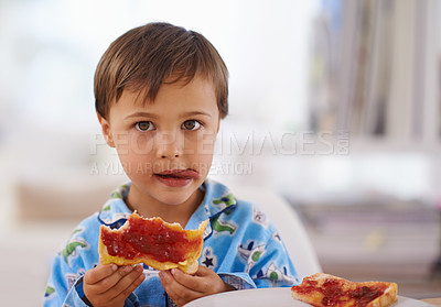 Buy stock photo A cute little boy eating toast with jam
