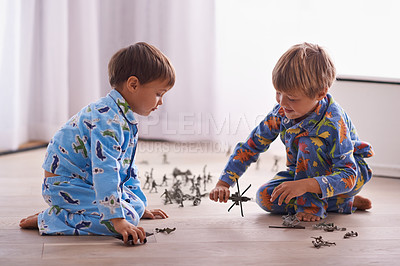 Buy stock photo Shot of two brothers playing together in their bedroom