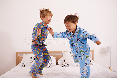 Buy stock photo Shot of two little boys jumping on the bed