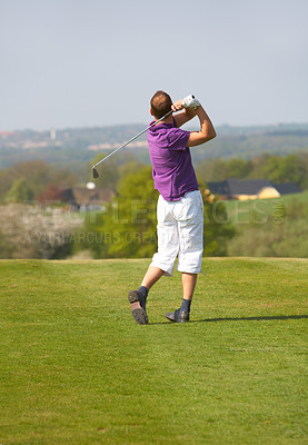 Buy stock photo A young golfer making a swin with a driver.