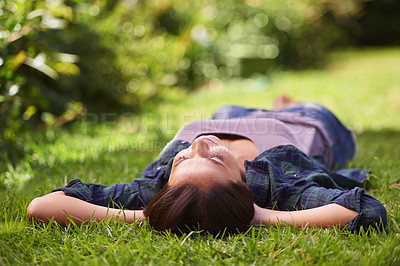 Buy stock photo Shot of an attractive young woman lying on the grass
