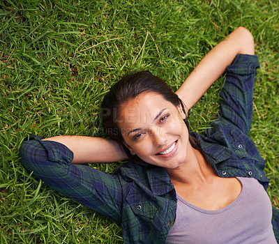 Buy stock photo High angle portrait of an attractive young woman lying on the grass