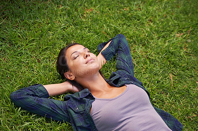 Buy stock photo High angle shot of an attractive young woman lying on the grass