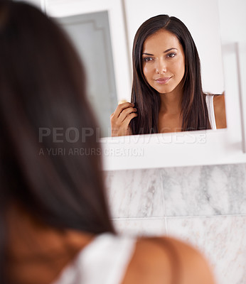 Buy stock photo Shot of a beautiful young woman looking at her face in the mirror