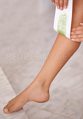 Buy stock photo Cropped shot of a woman waxing her lower leg