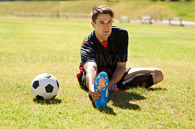 Buy stock photo Shot of a young footballer stretching on the field