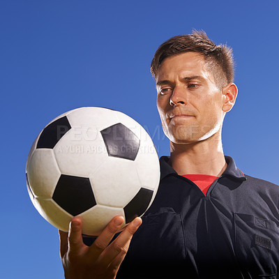 Buy stock photo Shot of a young footballer holding a ball in his hand