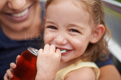Buy stock photo Portrait of a little girl drinking a soda on her mothers lap