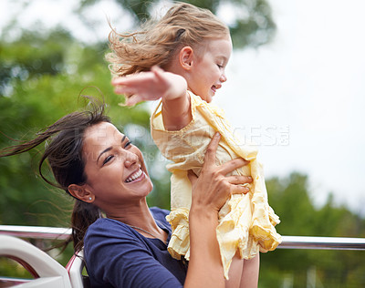 Buy stock photo Shot of a single mother lifting her daughter to the sky while sitting on a bus