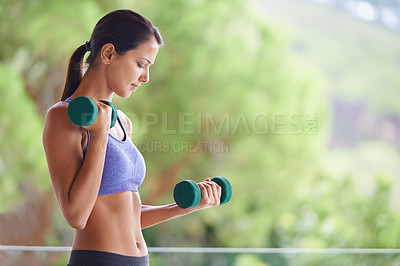 Buy stock photo A beautiful young woman lifting dumbbells outdoors