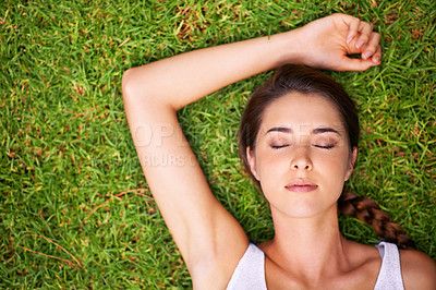 Buy stock photo A young woman lying on the grass outdoors